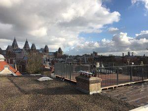 Dakterras met hardhouten terrasvlonder afgewerkt met Striphekwerk CT012-1200 RAL7016 uitzicht op het Rijks museam in Amsterdam